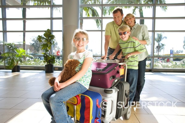Stock Photo: 4208R-22849 Family standing with luggage trolley in airport, girl 7-9 sitting on suitcase with soft toy in foreground, wearing sunglasses, smiling, portrait