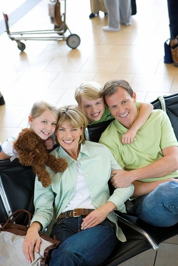 Family sitting in airport departure lounge, girl 7-9 holding soft toy, smiling, portrait, elevated view : Stock Photo