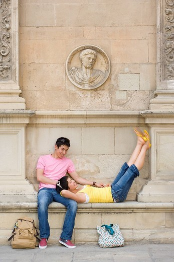 Stock Photo: 4208R-23354 Woman lying on man´s lap on bench in wall by bags on ground, smiling