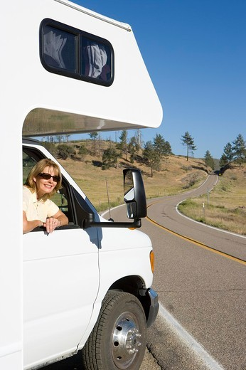 Woman leaning out of window of motor home, smiling, portrait : Stock Photo