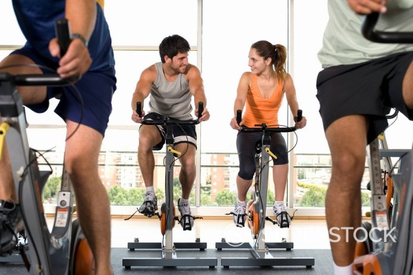 Man and woman on exercise bicycles in gym, smiling at each other, low angle view : Stock Photo