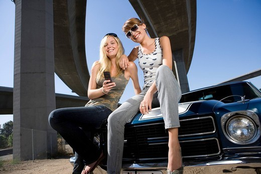 Two young women on bonnet of car beneath overpass, smiling, low angle view : Stock Photo