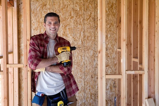 Builder with drill in partially built house, portrait : Stock Photo