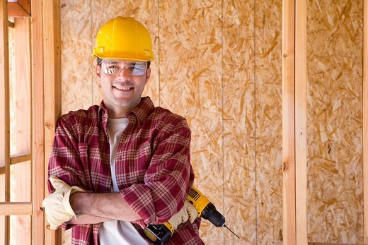 Stock Photo: 4208R-23534 Builder in hardhat with drill in partially built house, smiling, portrait