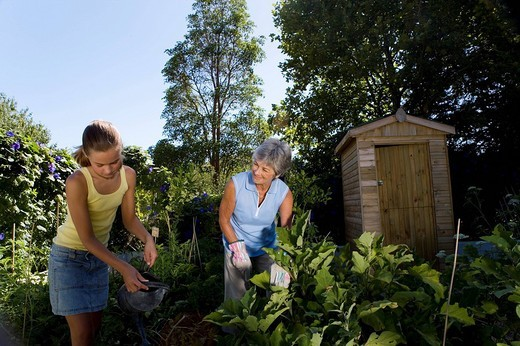 Mother and daughter 10_12 gardening, low angle view : Stock Photo