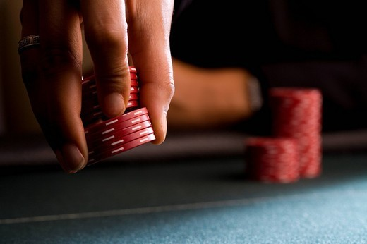Woman placing gambling chips on table, close-up : Stock Photo