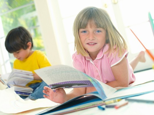 Girl 4-6 with book by friend 4-6, smiling, portrait tilt : Stock Photo
