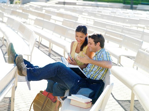 Stock Photo: 4208R-23914 Couple on bench outdoors, woman with mobile phone, smiling
