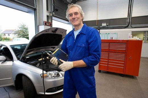 Mechanic with electronic diagnostics device by car, smiling, portrait : Stock Photo