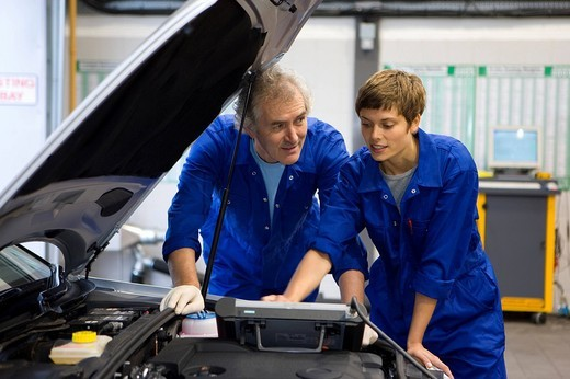Mechanic and colleague with electronic diagnostics device : Stock Photo