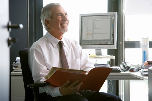 Senior businessman reviewing paperwork in office : Stock Photo