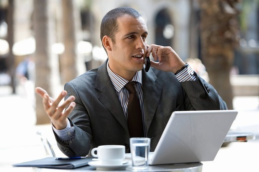 Stock Photo: 4208R-24085 Businessman talking on cell phone in cafe