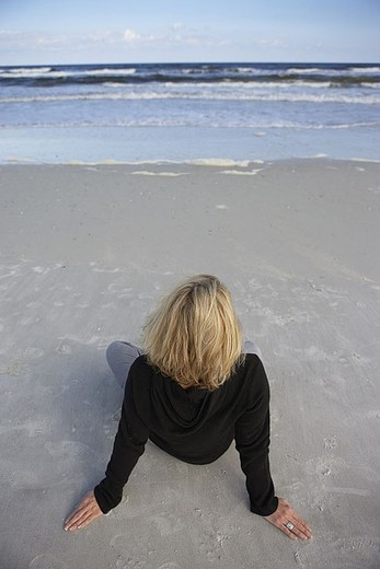 Stock Photo: 4208R-24116 Blonde woman wearing black jumper, sitting on sandy beach, looking at horizon over sea, rear view, elevated view tilt
