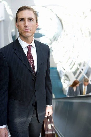 Businessman riding escalator : Stock Photo