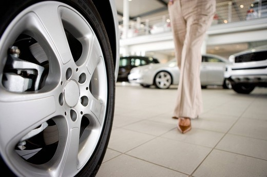 Woman walking in new car showroom : Stock Photo
