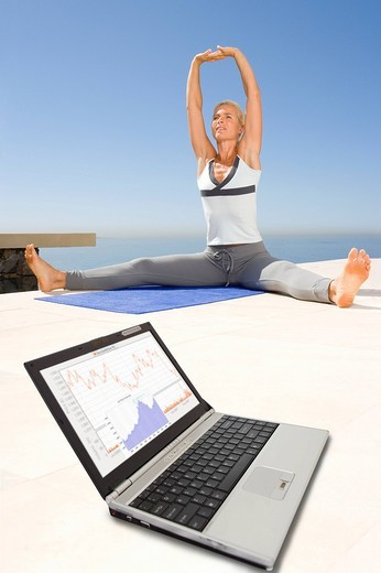 Stock Photo: 4208R-2433 Woman stretching on mat with financial figures on laptop in foreground