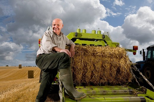 Portrait of farmer leaning on machinery with straw bale : Stock Photo