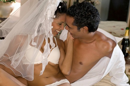 Young multi_ethnic couple in bed on their wedding night : Stock Photo