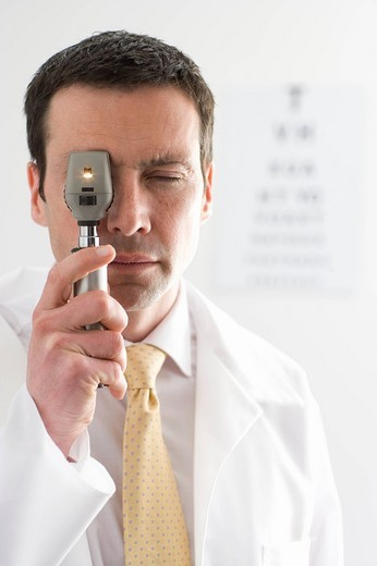 Doctor looking through ophthalmoscope with eye chart in background : Stock Photo