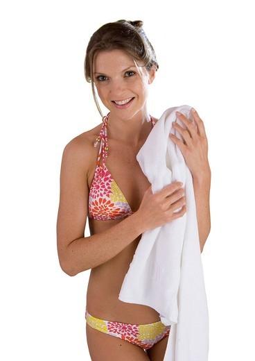 Stock Photo: 4208R-25602 Smiling woman in bikini holding towel