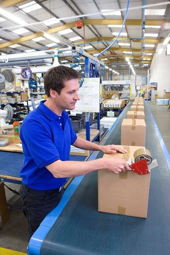 Worker in warehouse on assembly line taping cardboard box : Stock Photo