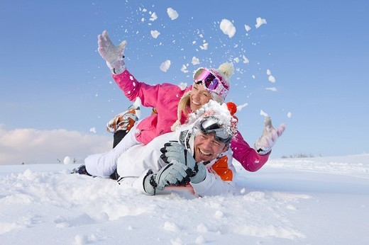 Couple laying together and throwing snow : Stock Photo