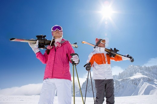 Skiers carrying skis and standing on ski slope : Stock Photo