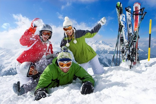 Stock Photo: 4208R-25872 Skis in snow and family having snowball fight on mountain top