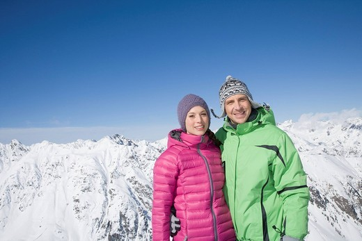 Stock Photo: 4208R-25975 Portrait of young couple in winter coats standing in mountains