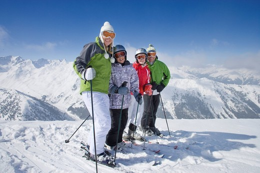Family of skiers smiling together on mountain top : Stock Photo