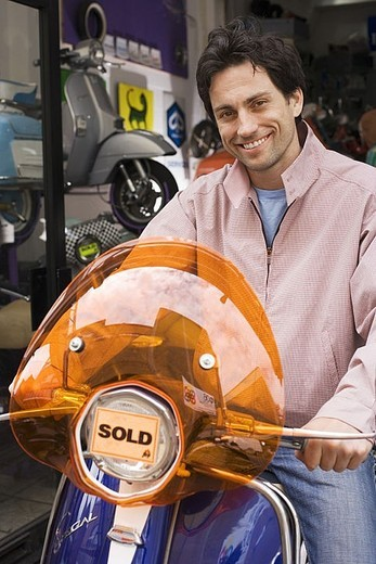 Stock Photo: 4208R-26297 Man standing outside shop with new scooter, orange sold sticker on headlight, smiling, portrait