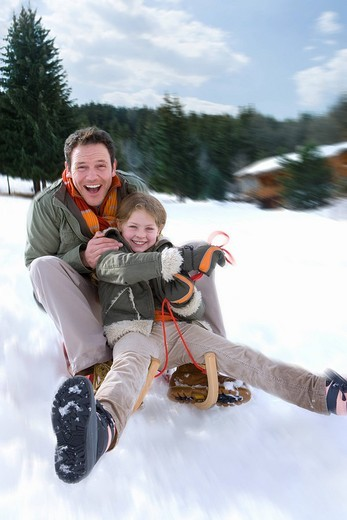 Father and daughter sledding down snow slope : Stock Photo