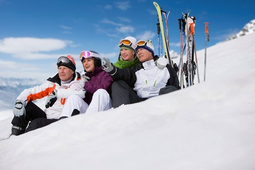 Skiers sitting in snow relaxing next to skis : Stock Photo