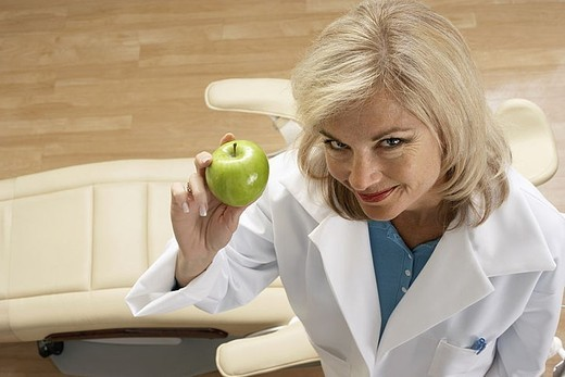 Stock Photo: 4208R-26718 Female dentist holding green apple in dental surgery, smiling, portrait, overhead view