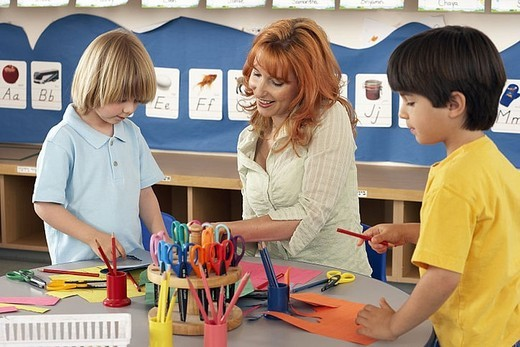 Two boys 4-6 making cards at desk in classroom, teacher assisting, smiling : Stock Photo
