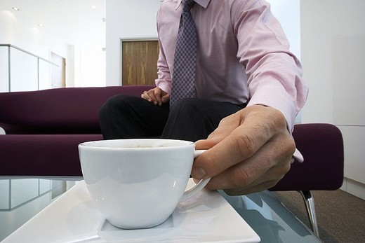 Businessman sitting on sofa in office lobby, placing cup on coffee table, close-up, surface level : Stock Photo