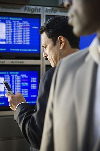 Two businessmen waiting in airport departure lounge, man reading text message on mobile phone differential focus : Stock Photo