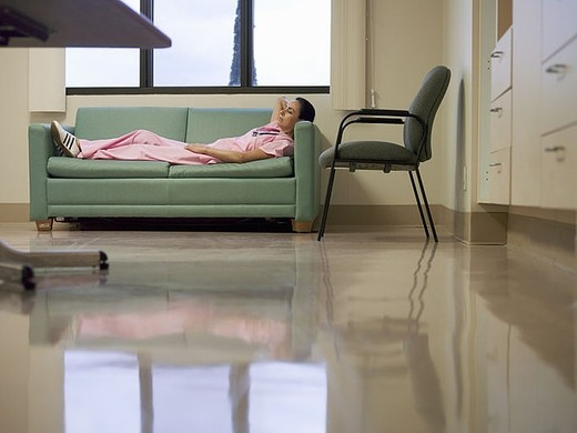 Nurse taking break in hospital staff room, lying on sofa, hands behind head, side view : Stock Photo