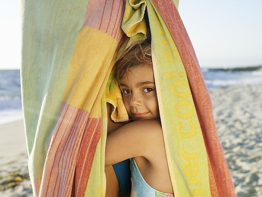 Stock Photo: 4208R-27128 Girl 5-7 snuggling up to mother wrapped in large towel on sandy beach, smiling, close-up, side view, portrait