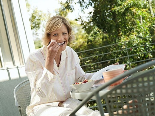 Woman sitting at balcony table, eating bowl of fresh strawberries, smiling, side view, portrait tilt : Stock Photo