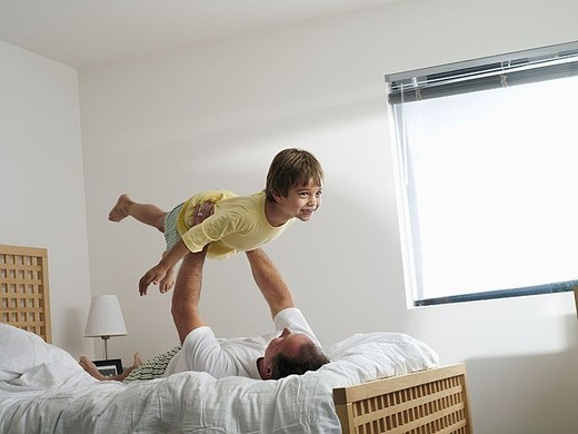 Stock Photo: 4208R-27146 Father and son 5-7 playing on double bed at home, man supporting boy in air, smiling, side view