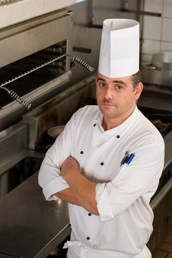 Male chef standing in commercial kitchen, arms folded, portrait, elevated view : Stock Photo