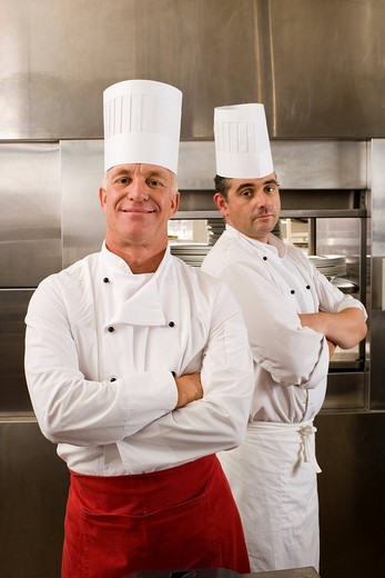 Two male chefs standing in commercial kitchen, arms folded, smiling, portrait : Stock Photo
