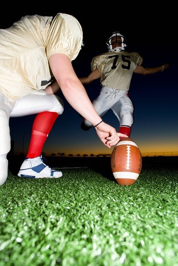 Stock Photo: 4208R-27268 American football player attempting to kick field goal, teammate holding ball vertically against pitch at sunset surface level