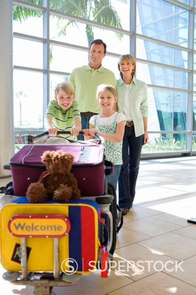 Stock Photo: 4208R-27396 Family standing beside luggage trolley in airport, smiling, front view, portrait, soft toy on suitcase