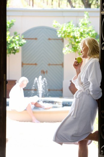 Mature couple wearing white bath robes, woman standing in doorway holding green apple in foregorund, side view : Stock Photo