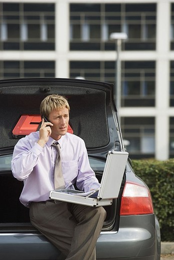 Businessman using mobile phone and laptop, sitting on open boot of stationary car : Stock Photo