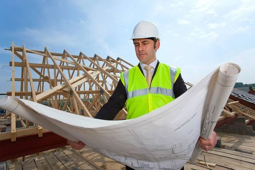Stock Photo: 4208R-27921 Architect reviewing blueprints at construction site