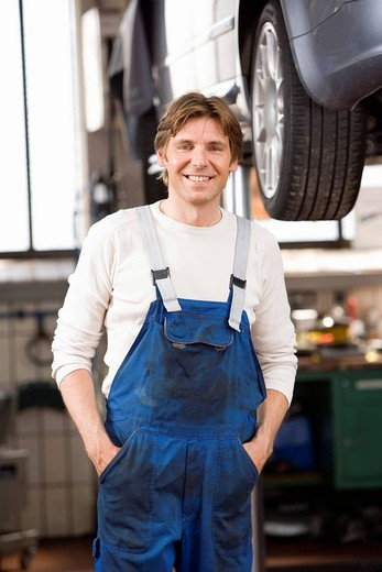 Mechanic posing in garage : Stock Photo