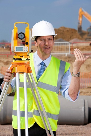 Stock Photo: 4208R-28210 Surveyor gesturing behind theodolite at construction site